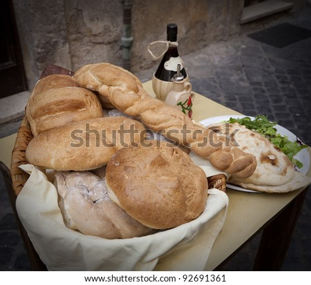 Various loaves in a basket and a bottle of wine seen outside a Roman restaurant. - stock photo
