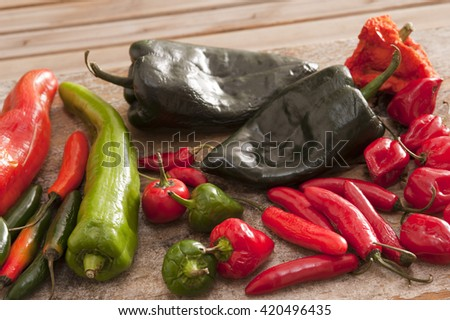 Various long, short, red, green and black hot peppers scattered on cutting board outdoors over wooden table - stock photo