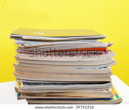 various magazines in pile over yellow background - stock photo