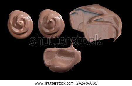 Various make up liquid powder strokes on black background - stock photo
