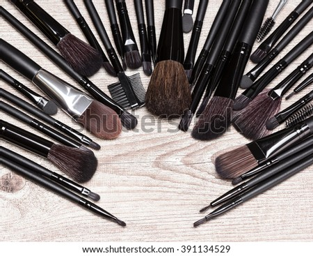 Various makeup brushes arranged in semicircle on shabby wooden surface. Professional tools of make-up artist. Round frame with small copy space in the center - stock photo