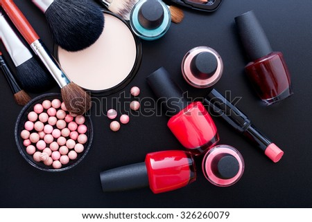 Various makeup products on dark background with copyspace. Cosmetics make up artist objects: lipstick, eye shadows, eyeliner, concealer, nail polish, powder, tools for make-up - stock photo