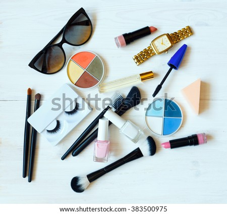 Various makeup products on white wooden background