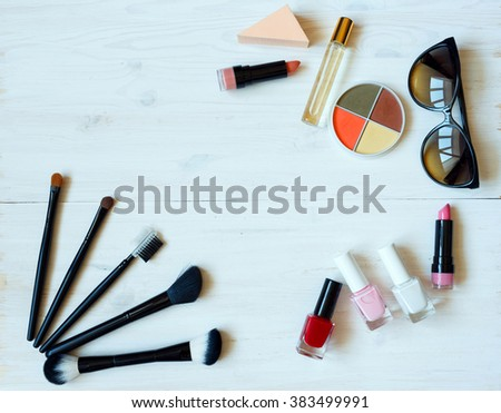 Various makeup products on white wooden background with copyspace