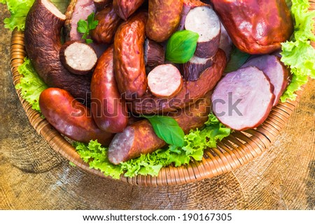 Various meat and sausage in a basket on a wooden table