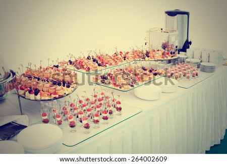 Various meat, fish and cheese banquet snacks on banquet table, toned image - stock photo