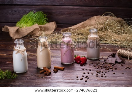 Various milkshakes on the wooden background of hay and sackcloth. - stock photo