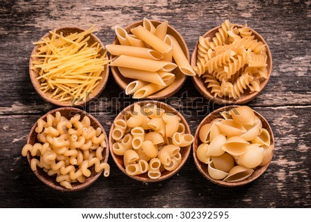 Various mix of pasta on wooden rustic background,  - stock photo