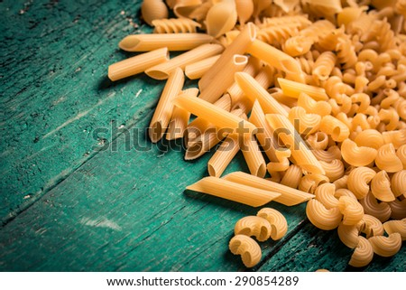 Various mix of pasta on wooden rustic background,  Diet and food concept. - stock photo