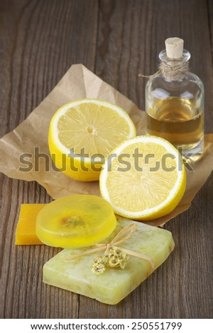 Various natural soaps, lemon and bottle of oil on rustic wooden background. - stock photo