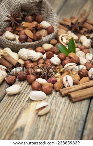 Various nuts in jute sack cinnamon sticks, star anise on a wooden background  - stock photo