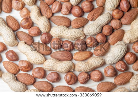 Various nuts in the round shaped heap on the wooden table