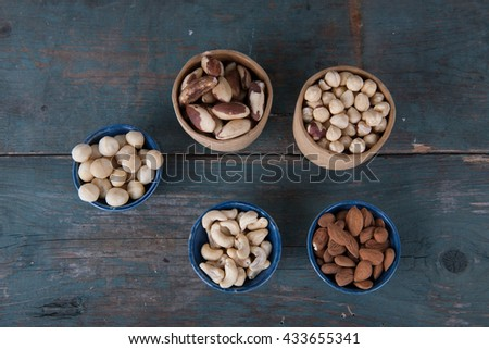 Various nuts on old wooden table - stock photo