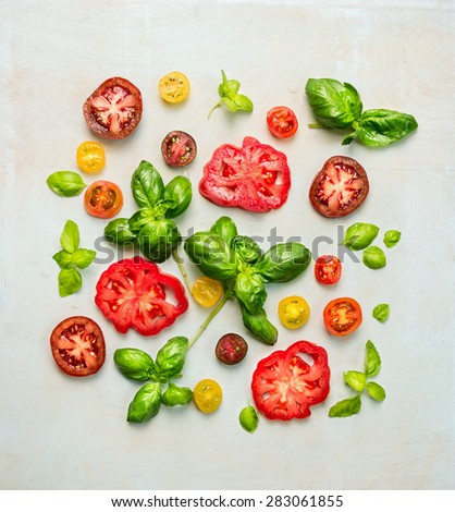 various of colorful sliced tomatoes with basil leaves, top view - stock photo
