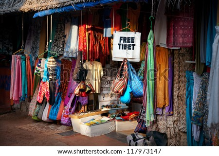 Various of different colorful clothes on Tibetan market and free Tibet banner in India