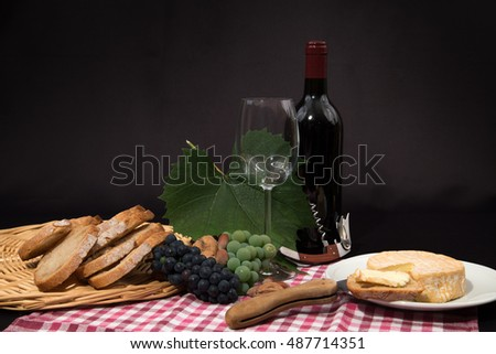 various of local specialty goat cheese, fruits and wine in front of black background
