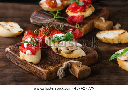 Various of mini bruschetta with tomatoes, strawberries, feta cheese, chicken, mushrooms and basil on toasted baguette, served on wood chopping board over wooden textured background.