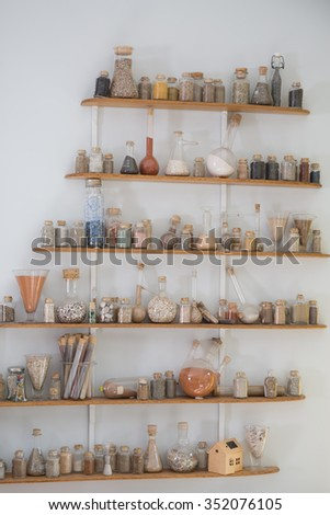 Various of powder spices in glass bottle jar on a wooden shelf ,  isolated on white background