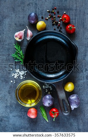 Various organic ingredients (potatoes, tomatoes, garlic and olive oil) over dark grunge background. Top view. Raw vegetables from garden for healthy cooking. - stock photo