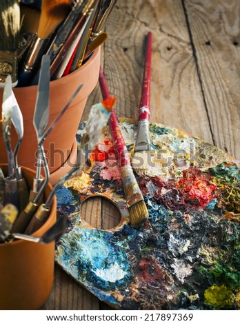 Various paint brushes and palette-knifes. Selective focus. Toned - stock photo