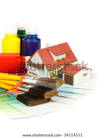 Various painting tools, miniature house and color guide on a white background