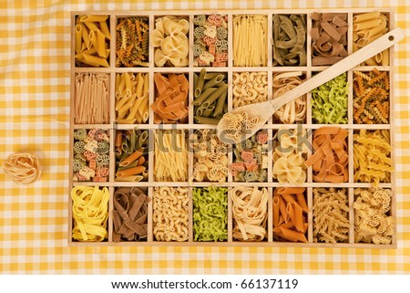 Various pasta sorts in wooden box.  Tagliatelle noodle still life. - stock photo