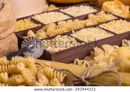 Various pasta types in the wooden box - stock photo