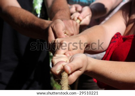 Various people are pulling together at a rope - stock photo