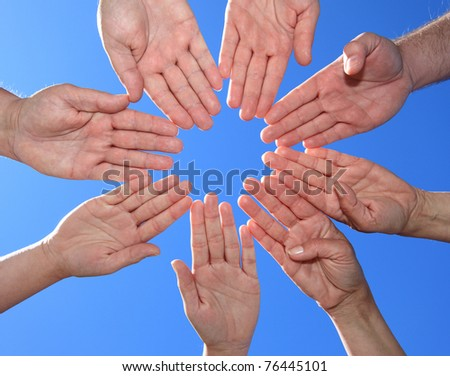 Various peoples hands in front of bright blue sky