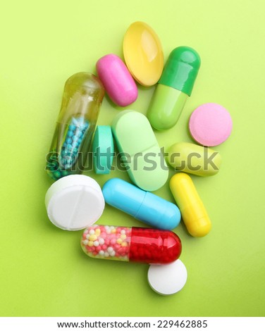 Various pharmaceuticals, pills on green background. - stock photo