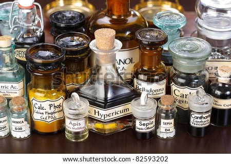 Various pharmacy bottles of homeopathic medicine on dark background - stock photo