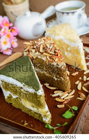 various pieces of cake with cup of tea on rustic wooden table