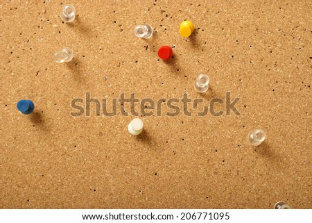 Various pins stuck into a corkboard for office use. - stock photo