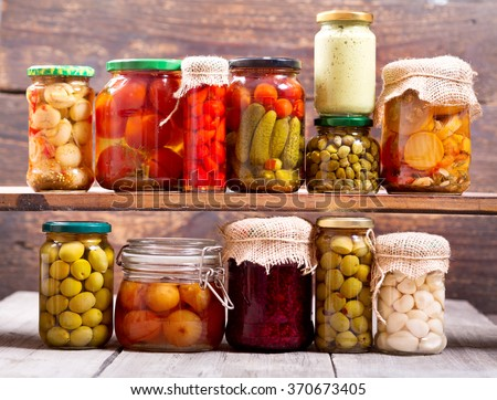 various preserved food on wooden background - stock photo