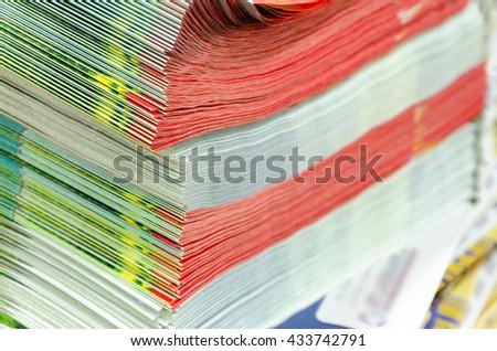 various print magazines in pile, closeup - stock photo