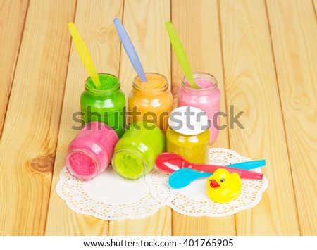 Various puree for baby food, spoons and rubber duck on a background of light wood. - stock photo