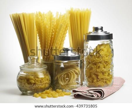 various raw pasta on the white background - stock photo