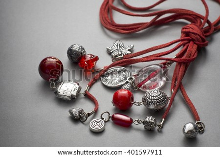 Various red stringed necklaces tied together with beads and trinkets over gray background - stock photo