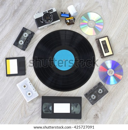 Various retro things. Camera, film, vinyl record disc, audio cassette, video cassette, floppy disc and CD