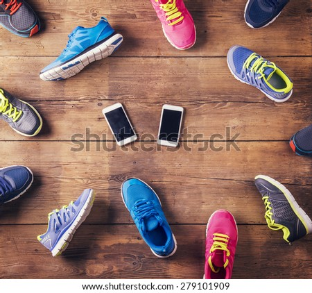 Various running shoes and two smart phones laid on a wooden floor background - stock photo