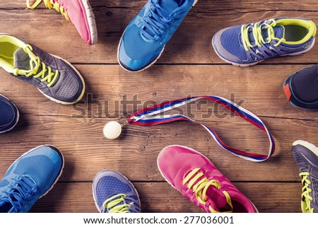 Various running shoes laid on a wooden floor background - stock photo
