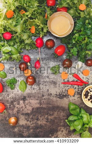 Various salad ingredients, vegetables and spices on concrete board. Top view, vintage toned image, blank space - stock photo