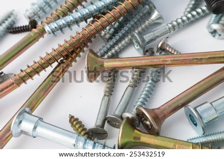 various screws and bolts close-up on a white background - stock photo
