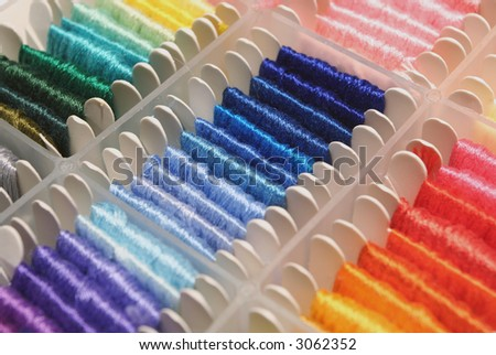 Various shades of blue and red embroidery thread on skeins. - stock photo