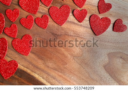 Various sizes of sparkly red Valentine's Day confetti frame the top of a rustic Cherry wood background, with copy-space.
