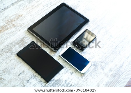 Various smartphones and Tablet Pcs on a wooden Table. - stock photo