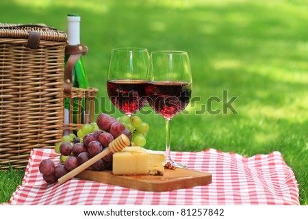 Various sorts of cheese, grapes and two glasses of the red wine