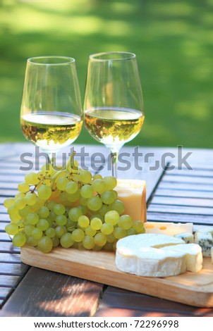 Various sorts of cheese, grapes and two glasses of the white wine - stock photo