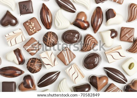 Various sorts of luxury confectionary chocolate on white - stock photo