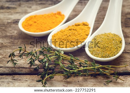 Various spice mix with branch of thyme on wooden table. Vintage spices background - stock photo